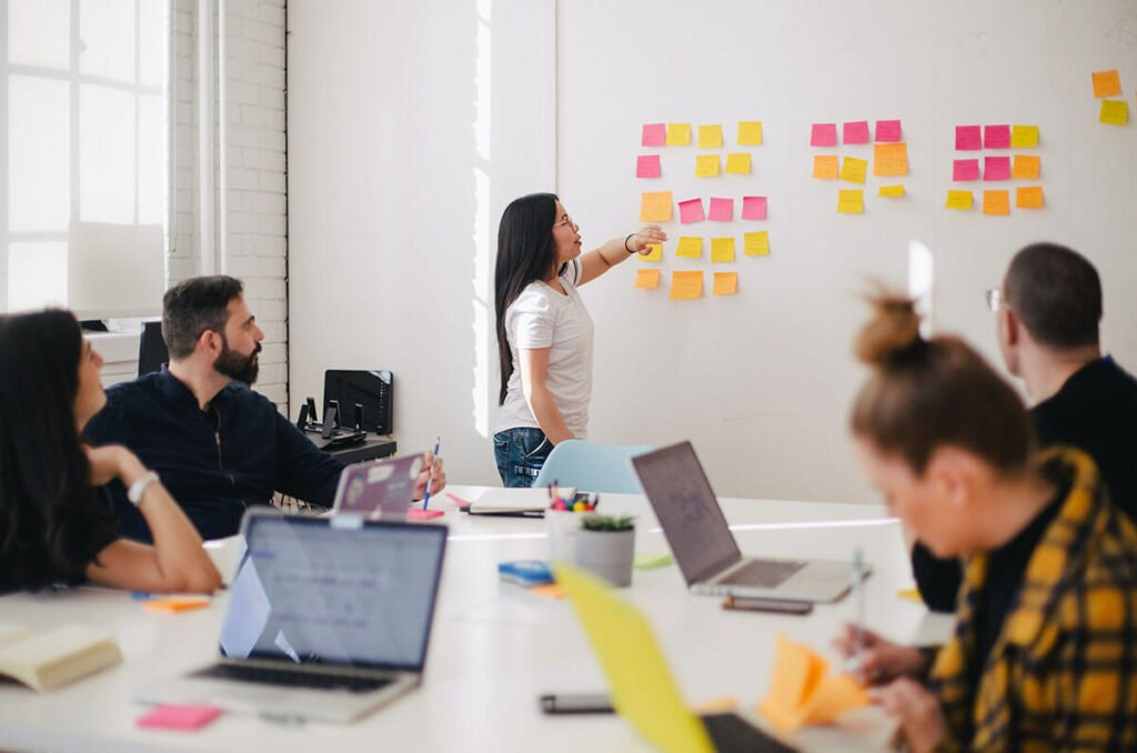 woman with sticky notes on wall in meeting room with team
